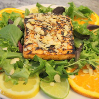 Asian Citrus Salmon Salad is marinated with the sweet and citrus flavors of orange, lemon, lime and honey and the Asian flavors of sesame, soy sauce, garlic and ginger and topped with almonds.